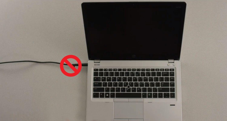 ノートパソコンの電源ケーブルの上に、電源ケーブルを外してから取り付けるように注意を促す斜線入りの円を表示