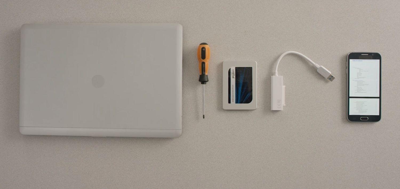 机上に並べられたノートパソコン、Crucial SSD、ドライバー、パソコンのオーナーズマニュアル