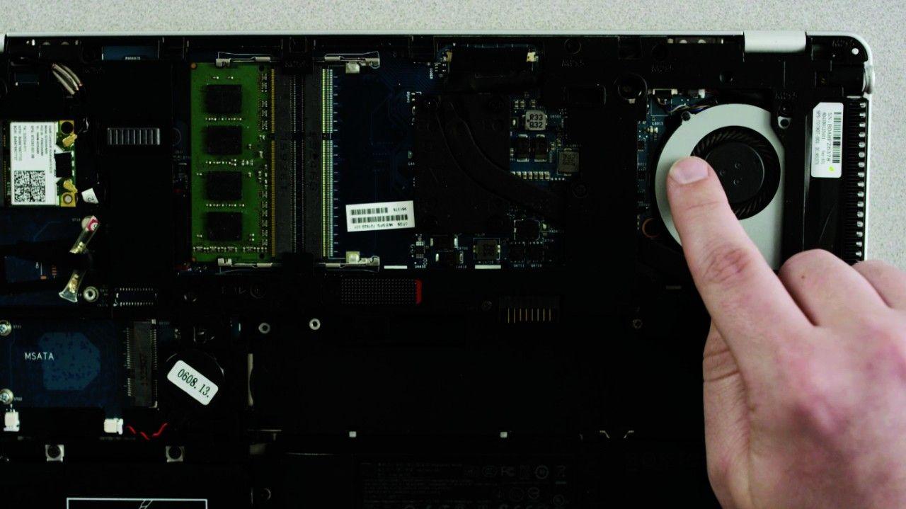 人が指でノートブックの塗装されていない金属面に触れて静電気を放電しているところ