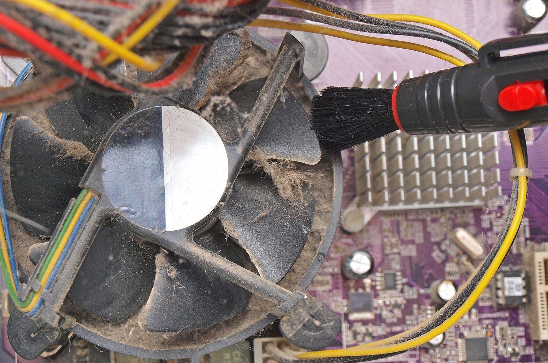 デスクトップパソコンの露出したファンから小型ブラシで埃や糸くずを取り除いているところ