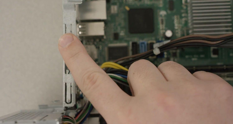 人が指でパソコンの塗装されていない金属面に触れて静電気を放電しているところ