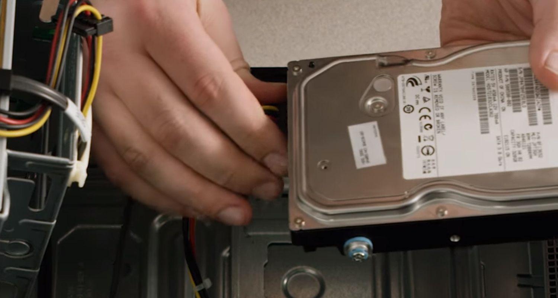 デスクトップパソコンのストレージドライブからケーブルを取り外しているところ